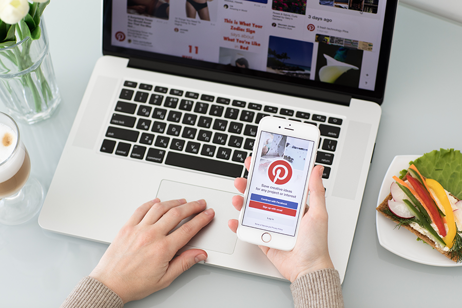 image of a person holding an iphone with the pinterest app open in front of a laptop